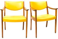 Hello yellow: sleek pair of mid-century armchairs with leather seats and backs.
