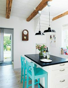 white kitchen, teal barstools, black countertops/lights