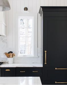 The tall window and tall black cabinet make the spoons in the left corner appear to be much smaller than they actually are.