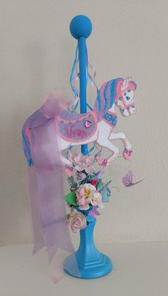This carousel is handmade, hand drawn, hand cut and hand painted. Decorated with lots of different colored, shaped and textured flowers as well as many different rhinestones with various shapes and colors, and much more. This centerpiece is also a beautiful keepsake decoration, place