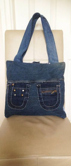 Handmade tote handbag is made from an assortment of recycled jeans fabrics. On the front of the bag I have used jeans belts, a buckle, patches, pockets with metal zips and a ring to display your favourite key ring or bag charm. On the reverse side of the bag I have used two recycled