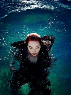 Young woman with red hair and a flowing black dress floating in dark blue and…