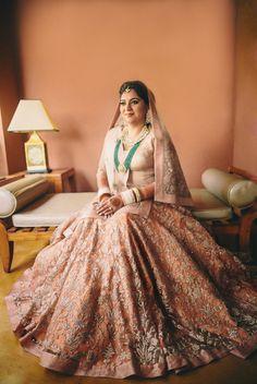 elegant pastel peach bridal lehenga with long top, plus sized brides, heavy brides, gold top, long emerald necklace, contrast jewellery, morning wedding, beach wedding, peach