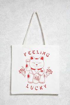 """A canvas tote bag featuring a front """"Feeling Lucky"""" graphic with a waving Maneki-neko cat and two top handles."""