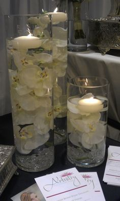 Tall vases with flowers in water and floating candles