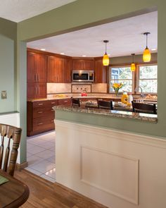 Kitchen in Nashua, NH. Placing the same granite on the island and as a cap on the half wall towards the dining area provided a sense of transition into the space to enhance the flow between the rooms. www.gmroth.com