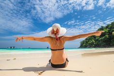Happy woman on Similan Islands - Beautiful and happy woman with swimsuit and wide-brimmed hat on white sand tropical beach. Similan Islands National Park, Phang Nga, Thailand, one of the tourist attraction of Andaman Sea