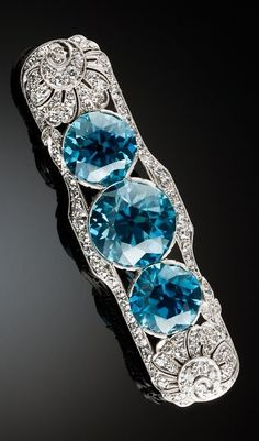 Walton & Co. - An Art Deco platinum, blue zircon and diamond brooch, 1920s - pre 1927. A striking and finely made Art Deco brooch featuring a natural large vivid blue zircon in the centre flanked by natural vivid blue zircons with stylised flower terminals in a pierced and railed surround of diamonds set in platinum. 5.7 x 1.7cm.