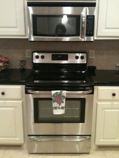 dark countertops with light cabinets and tile.