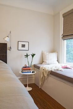 Using the dead space along a bedroom wall can become a private reading corner. This lamp and table work for both the bed and window seat