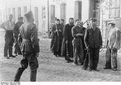 Polish Jews are lined up by German soldiers to do forced labor, September 1939.