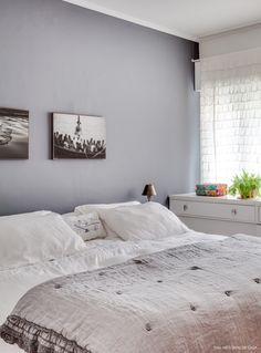 Quarto de casal com parede e roupa de cama cinza.