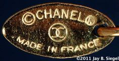 Chanel Oval Mark - 1980s    - Photo by Jay B. Siegel      Another type of oval Chanel signature cartouche, which can be found both soldered on and used as a hang tag (as shown here) on a variety of pieces. The season number is not included on these tags dating to the 1980s.