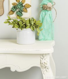 A thrifted side table goes vintage when you add painted-to-match metal accents–we covered the flower and table with chalky finish paint and secured the flower with glue.