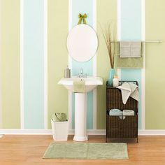 Get the look by painting your bathroom wall white, then taping off evenly sized stripes. Paint the stripes the same color, or use two coordinating colors like the ones shown here.
