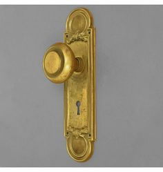 Regal Doorset, c.1900. The circle motif at the top and bottom of the escutcheons echoes the pleasantly simple design of the knobs. Made of stamped steel with brass plating. The brass has acquired a patina and is lightly worn.