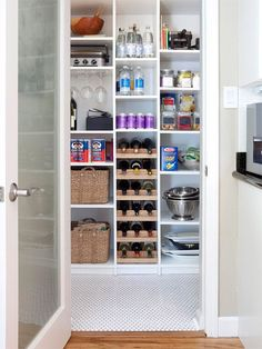 a standard closet became an efficient pantry. A shelving system from a closet company proved cost-effective, although the homeowners built their own wine racks to save money. Classic white penny tile replaced old linoleum flooring, setting a stylish foundation for the storage area.