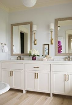 Blue elegant bathroom design with soft white bathroom cabinets, double sinks, marble counter tops, mirrors, sconces, light oak floors and soft blue walls paint color. white blue bathroom colors.