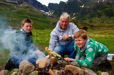 A father and two boys making twistbread on a bonfire