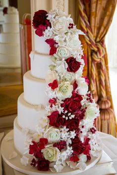 Festive red hues and romantic roses wowed guests at Alice and Allan's big day, as seen in Your Berks, Bucks & Oxon Wedding, issue 50. Cake by Petit Gateau (www.weddingcakesberkshire.com) Image by David Bostock Photography (www.thebridalphotographer.co.uk)