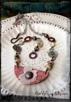 A necklace I made with a vintage three-pence made into a button, vintage mother of pearl buttons, rhinestones, and copper.    via www.PrettyThingsBlog.com