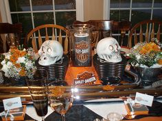 "the idea for two cylinders as a centerpiece which were put around a glass vase with a HD print-out inside and a HD bandana tied around. The pipes (heat shields) became a ""runner"" down the length of the table. Used the skulls for a ""bad biker"" look as well as the Halloween time of year."