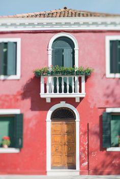 A brilliantly red rose colored home in Burano, Venice.