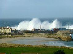 Waves crashing over the breakwater at Braye Harbour, Alderney
