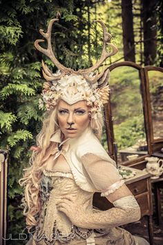 Make a strong visual statement with this exquisite, massive, and beautiful piece. All hail the Queen of the Forest! <3  This unique and opulent headdress features huge 10 point buck antlers cast in resin from the original idolatre sculpture (which means they are 100% vegan from start to finish), and faun ears cast in resin from the original idolatre sculptures. All pieces are hand painted with exquisite attention to detail. It gracefully circles the head in faux flowers, beautiful beaded…