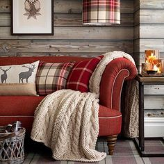A cosy living room with red festive sofa, tartan cushions and a big wool throw