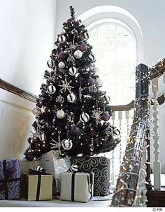 white and silver decorations on black Christmas tree...