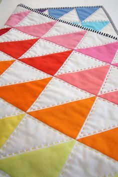 "Tied with a Ribbon – ""This quilt is a cot size quilt that I have named Rainbow Fizz and is one of the projects for Term 2 Sewing classes together with Claire Turpin Design.  After using a Kona Solids Charm pack from Pink Chalk as the inspiration I set to turn the squares into triangles."" 