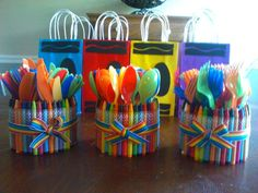 Crayola or crayon themed party. Homemade utensil holders. The cans are from Great Value (Wal-Mart) beef stew as they are a bit wider than a regular soup can.  Crayons are up&up brand (Target) and are held on with a few rubber bands so they can be used again. Ribbon is hot glued to rubber bands, bow is hot glued to ribbon.  Gift/favor bags in background.
