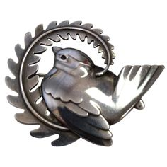 A 1930s-40s silver brooch by Georg Jensen featuring a dove and palm branch, a symbol of peace.