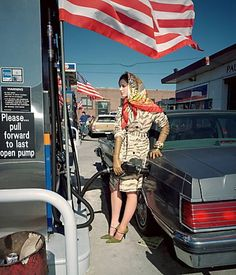 Martin Parr. I like this photograph as it's showing off the ladies wealth by the way she's standing, dressed and what looks like the car she is driving. The photograph is in composition with the first horizontal third line on the horizon of the photograph.