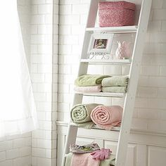 Coolest Bathroom Decor idea - simple ladder against the wall adds storage space and the different levels make it look lively!