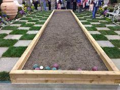 Backyard bocce court and checkered grass.