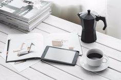 Digital tablet with cup of coffee on a white desk · Free Stock Photo