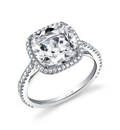 This Magnificent 18K white gold diamond engagement ring features a 1.5 carat cushion cut center diamond. Accentuated by surrounding diamonds and diamonds flowing down the sides totaling 0.36 carats. The diamond engagement ring is available in any shape or size center diamond, in 18K white gold or platinum. All Sylvie Collection diamond engagement rings are available with a flush fit matching wedding band.