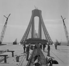 Construction workers wearing hardhats work tirelessly on the construction of the Verrazano Bridge ahead of its completion in 1964.