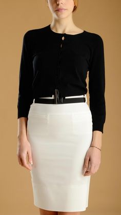 Long sleeve, crew neck cropped cardigan and a white skirt.