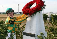 Julien Leparoux places a wreath on the grave of Black Gold at the Fair Gounds in 2008. It is a tradition that after the running of the Black Gold Stakes, the winning jockey places a wreath on the grave.