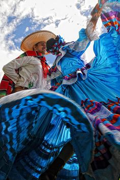 This couple is dancing the Mariachi, a traditional courtship dance. Women wave their colorful dresses to the rhythm of the music, keeping men at a safe distance!