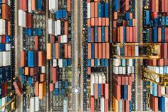 A drone shot of stacks of large shipping containers in a port