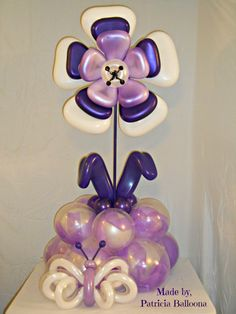 Purple and white spring flower balloon bouquet with butterfly. For an extra special effect, Patricia put ribbons into the base balloons. Balloon Tower, Balloon Display, Balloon Backdrop, Balloon Columns, Balloon Table Centerpieces, Balloon Arrangements, Balloon Decorations, Balloon Ideas, Balloon Crafts