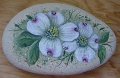 dogwood blossoms painted on a rock