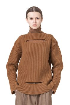 This extravagant pure merino wool piece can be worn on its own to reveal a hint of skin through the slits, or intertwined with the chunky turtleneck accessory. The extra fine wool is achieved by a slow spinning process providing very even and smooth yarns. This piece is fully fashioned and suitable for home cold water hand wash. Produced in Slovakia Fabric origin: Italy Composition:heather caramel 100% supergeelong two-endfine merino wool; GG 5; prewashed