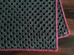 Granny square blanket, grey with pink edging.