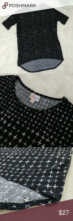 """LULAROE Irma Black and White Cross Tunic Top Preowned Lularoe Irma tunic top featuring a black and white cross design. Low/high length.  Measurementstaken laying flat across:   Armpit to armpit 26"""" Back side 34"""" long Front side 28"""" long  Very loose and comfortable fit, size Xsmall. 95% polyester, 5% spandex. Machine wash cold. LuLaRoe Tops"""