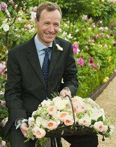Chelsea Flower Show - David Austin Roses.  David Austin holding a basket of Patience and...Emily?...roses